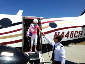 AFW volunteer pilot Christopher Gaertner gives Emily a hand en route to Stanford's Lucile Packard Children's Hospital for treatment.