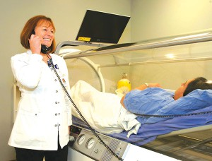 Diane Bakke, RN, speaks with a patient in the center's new hyperbaric oxygen chamber.