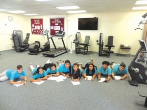 Students write in their health journals after fitness class
